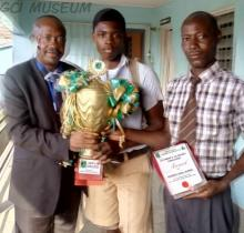 The GCI Principal, Dr Tunde Odekunle, GCI Hockey Team member and GCI Sportsmaster; flaunting the trophy and award won by GCI at the 2018 Under-16 South West Hockey Foundation Tournament.